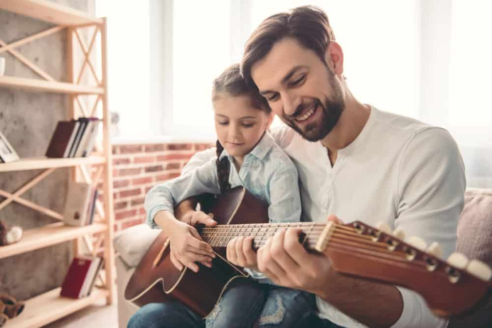 father and child playing the guitar